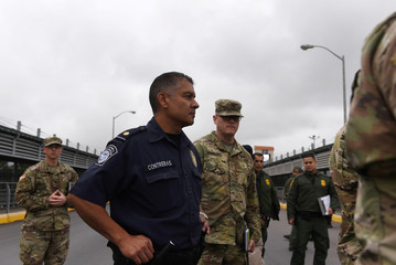 U.S. Customs and Border Protection officers and members of the U.S. Army stand during a tour of the Hidalgo International Bridge in Hidalgo