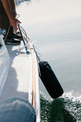 Man lifting up bumpers on the side of his boat out at sea