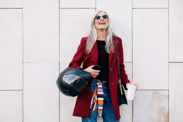 Portrait of a fashion mature woman smiling on the street.