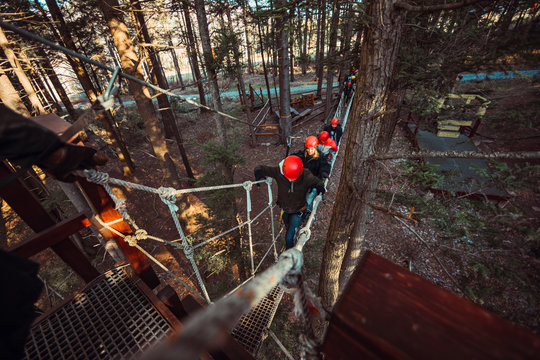 Friends follow the leader through an outdoor rope bridge on a zip line course