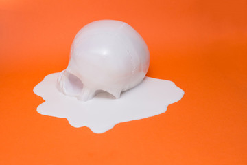 A white Skull melting on an orange backdrop