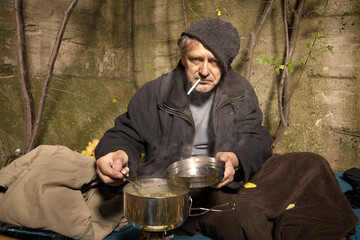 Ugly pauper man living outdoor preparing and eating lentil soup