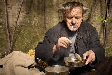 Ugly pauper man living outdoor preparing and eating lentil soup