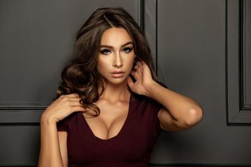 Sensual beautiful brunette woman posing in dress. Girl with long curly hair.