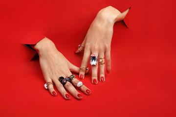Obraz Czerwone paznokcie.  Kobiece dłonie na czerwonym tle. Palce z pierścionkami. - fototapety do salonu