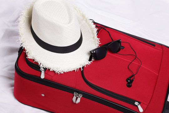 A white straw hat and black sunglasses over a red suitcase