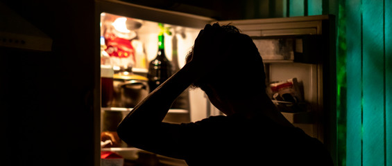 man standing near the opened fridge to pick some food at night at home f