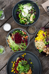 rustic table filled with colourful salads