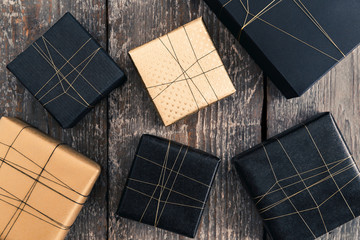 Six gifts wrapped in black and gold on wooden surface
