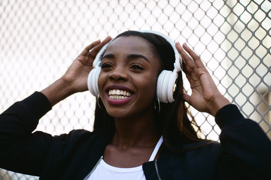 Portrait of a cool young woman listening music on headphones standing on the street.