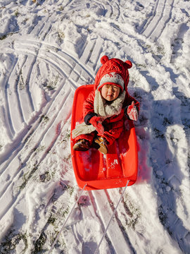 Baby on sled doing thumbs up