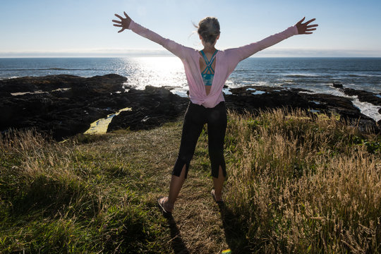 Adult female stands with her arms raised in happiness and freedom while on vacation at Cape Perpetua along the Oregon coastline