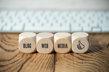 """Würfel mit Aufschriften """"Blog"""", """"Web"""", """"Media"""" und """"Gefällt mir""""-Symbol vor einer Tastatur"""
