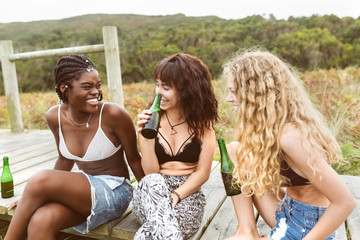 Three young women drinking beer and having fun outdoors