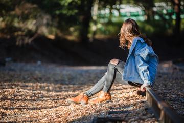 Teenage girl sitting on the train tracks at dusk