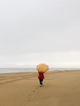 A woman with an umbrella on a beach