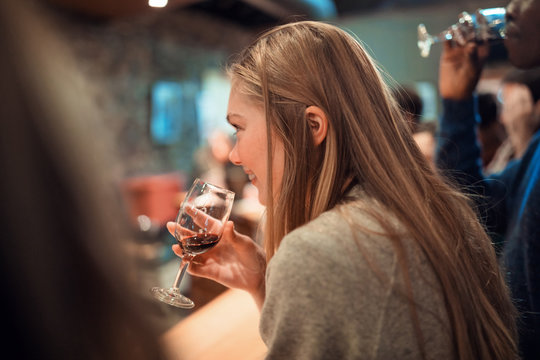 Young woman enjoying herself at a wine tasting event with friends