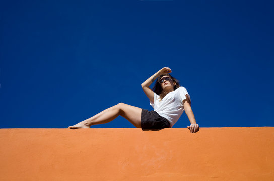 Young woman sitting on wall against blue sky