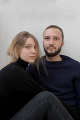 young beautiful fashionable couple on the white background of the wall sensually sit together