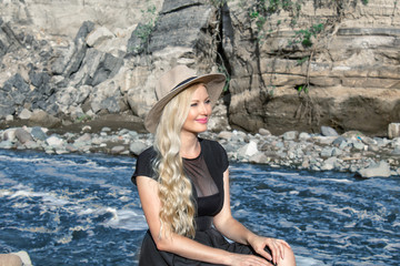 Beautiful young woman blonde with long hair in a hat sitting on a rocky shore by the river and relaxing. Around the mountains and rocky landscape.