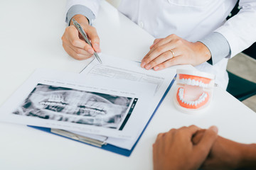 Dentist hand holding pen pointing x-ray picture and talking to the patient about medication and surgery treatment.