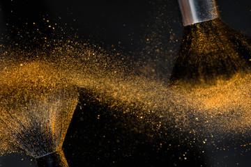 Make-up brushes with golden face powder against dark background