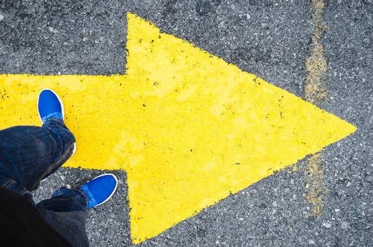 close up on the legs of a man standing on a yellow arrow in the direction to the right, concept of decisions in life.