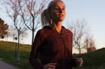 Young woman running in sunset