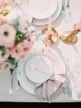 A wedding setting with a beautiful plates, napkins and flowers