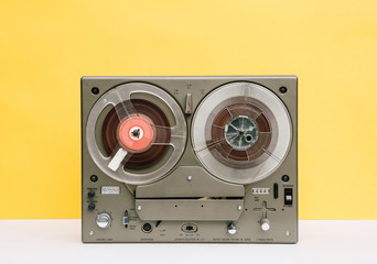 Vintage reel to reel in front of a yellow background