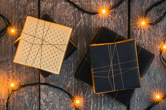Four gifts on wooden surface surrounded by christmas lights