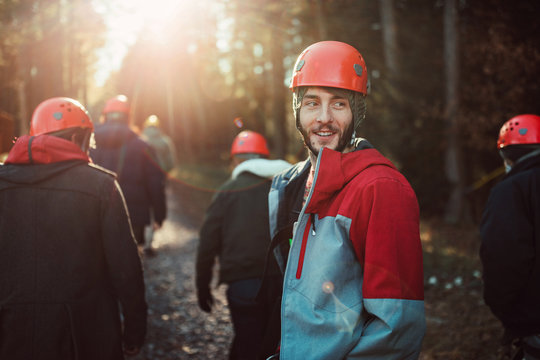 young man looks back at his friends while walking through the woods during an outdoor zip line adventure