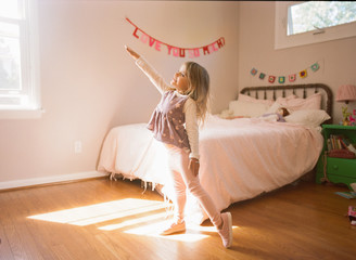 Little girl practicing ballet moves in her room