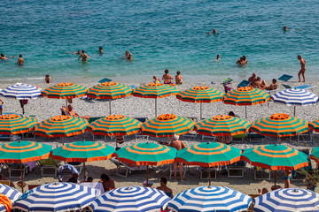 People swimming and sunbathing on the beach at Monterosso al Mare on the Ligurian coast, Italy