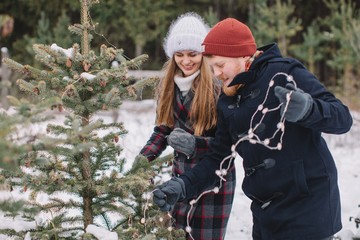 Lovely couple decorating Christmas tree outdoors