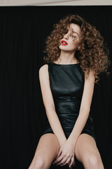 Front view portrait of young attractive woman with curly hair and red lips posing on black background with closed eyes