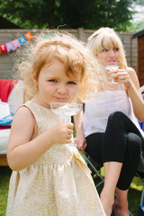 Little girl drinks lemonade while her mum drinks champagne at a garden party.