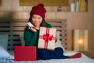 young beautiful and happy Asian Chinese woman holding credit card and Christmas gift box shopping online xmas presents at home bed smiling satisfied