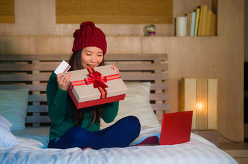 young beautiful happy Asian Japanese girl holding credit card and Christmas gift box shopping online xmas presents smiling satisfied at home bed