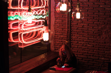 Woman relaxing?in night cafe