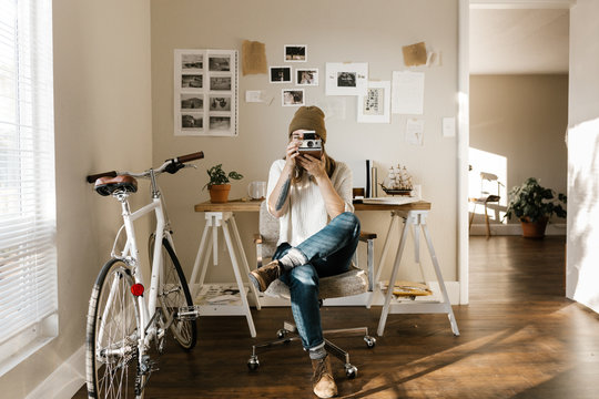 photographer in home studio with instant camera