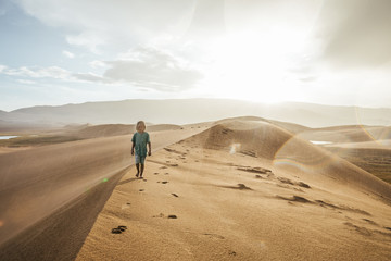 little blonde boy walking on a sand dune in heavy rain at sunset