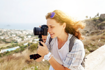 Beautiful young woman with a camera in hand, traveler and bloggen on the background of a beautiful landscape with mountains and sea