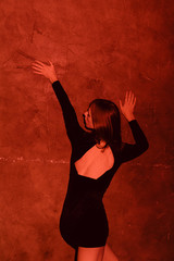 young androgyne man in small black dress dancing