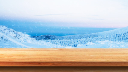 Empty wooden tabletop against Scenic view of snow monster in winter. For your product placement or montage with focus to the table top in the foreground