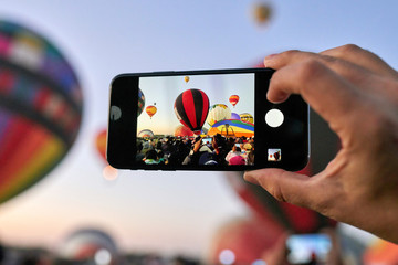 Person taking a photo with a cell phone at a hot air balloon liftoff