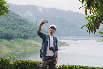 Cheerful young Asian traveler man taking photo or selfie with mobile smart phone outdoors scenic background. Lifestyle and relaxation concept.