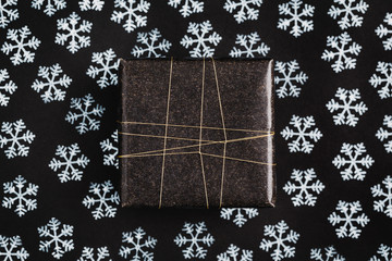 Gift wrapped in black on black background with snow stamps