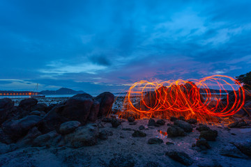 light lines of steel wool with long exposure speed motion abstract at sunrise on the rock.