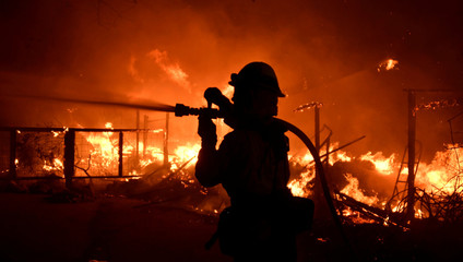 A firefighter hoses down a property engulfed in flames during the Woolsey Fire in Malibu
